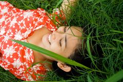 Woman lying on green grass Stock Photo