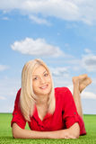 Woman lying on a green grass field outdoors Royalty Free Stock Images