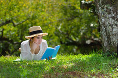 Woman lying on green grass reading a book in the park Stock Image