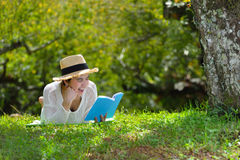 Woman lying on green grass reading a book in the park Royalty Free Stock Photo
