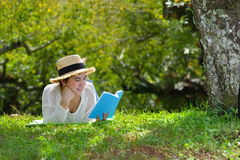 Woman lying on green grass reading a book in the park Royalty Free Stock Photography