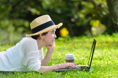 Woman lying on green grass using laptop computer in the park Royalty Free Stock Image