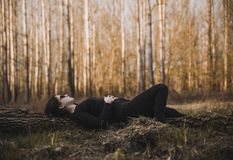 Woman Lying on the Ground Surrounded by Bare Trees Stock Photography