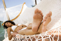 Woman lying in a hammock on a boat in the sun, wearing a white bikini Stock Photography