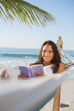 Woman lying on hammock holding book and smiling at camera Stock Image