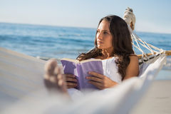 Woman lying on hammock holding book and thinking Royalty Free Stock Photos