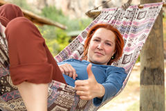 Woman lying in Hammock at Patio of Wooden Rural Cottage with OK gesture. Woman lying in Hammock at Patio of Wooden Rural Cottage making OK hand Gesture Smiling Royalty Free Stock Photography