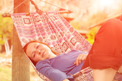 Woman lying in Hammock at Patio of Wooden Rural Cottage. Relaxed and serene smiling positive green Garden on background Royalty Free Stock Photos