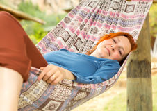Woman lying in Hammock at Patio of Wooden Rural Cottage. Relaxed and serene smiling positive green Garden on background Royalty Free Stock Photography