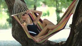 Woman lying in hammock in tree's shadow on beach stock footage