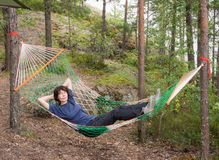 Woman lying in a hammock. In the woods Stock Image