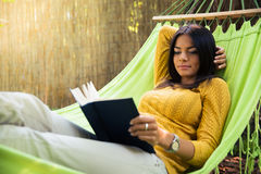 Woman lying on hammok and reading book Royalty Free Stock Image