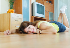 Woman lying on hardwood floor Royalty Free Stock Image