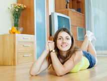 Woman lying on hardwood floor Royalty Free Stock Photography