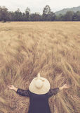 Woman lying with hat hide her face on yellow field grass. Relax. Asian woman lying with hat hide her face on yellow field grass. Relax or holiday concept Stock Images