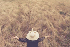Woman lying with hat hide her face on yellow field grass. Relax. Asian woman lying with hat hide her face on yellow field grass. Relax or holiday concept Royalty Free Stock Images