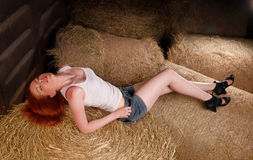 Woman lying on a haystack Stock Photo