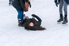 Woman lying on her back on the ice when skating at a public ice skating rink. Stock Photo