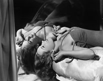 Woman lying on her back next to mirror Stock Images