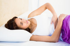 Woman lying on her bed with a belly pain Royalty Free Stock Photography