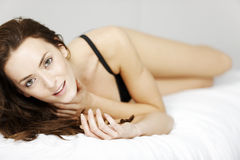 Woman lying on her bed Stock Images