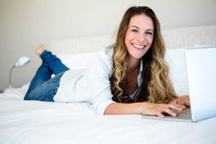 woman lying on her bed on her laptop Stock Images