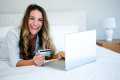 woman lying on her bed on her laptop Stock Photos