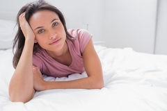 Woman lying on her bed and holding her head Royalty Free Stock Photo