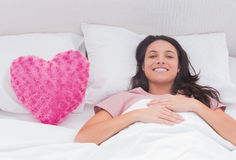 Woman lying in her bed next to a pink heart pillow Royalty Free Stock Photography