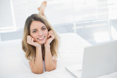 Woman lying on her bed smiling cheerfully at camera Stock Photography
