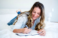Woman lying on her bed writing in a book. Woman lying on her bed, smiling at the camera and writing in a book with a pen Royalty Free Stock Photo