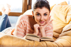Woman lying on her couch reading a book at home Royalty Free Stock Image