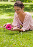 Woman lying on her front while holding a flower Stock Photo