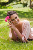 Woman lying on her front while holding a flower against her head Royalty Free Stock Images