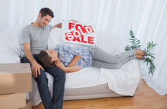 Woman lying on her husband in the couch in their new house Stock Image
