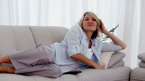 Woman lying on her sofa and watching television stock video