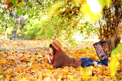 Woman lying on her stomach on autumn leaves. Stock Photo