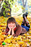 Woman lying on her stomach on autumn leaves. Stock Images
