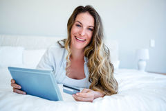 woman lying on her tablet holding her credit card Royalty Free Stock Photo