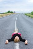 Woman lying on the highway road Stock Photos