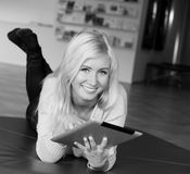 Woman lying holding tablet. Smiling relaxed female lying and holding-using a tablet royalty free stock image