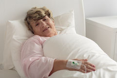 Woman lying in hospital bed Stock Image