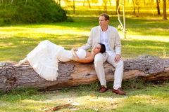 Woman lying on husband leg in a park trunk Royalty Free Stock Image