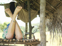 Woman Lying In Hut With Bare Legs Crossed Stock Image