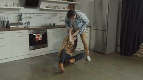 Woman lying on kitchen floor fighting off rude man. Rude man twisting woman hands, attacking defenseless victim lying on floor in domnestic kitchen. Aggressive stock video