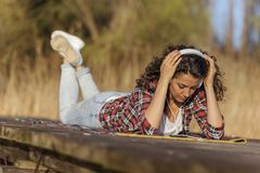 Woman lying on the docks listening to the music royalty free stock photo