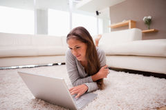 Woman lying with laptop on the floor Royalty Free Stock Photography