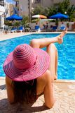 Woman lying by a large swimming pool on holiday Royalty Free Stock Photo