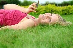 Woman lying on a lawn Stock Photos
