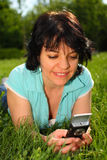 Woman lying on the lawn using mobile. Smiling brunette woman in T-shirt lying on the lawn using mobile Stock Photo